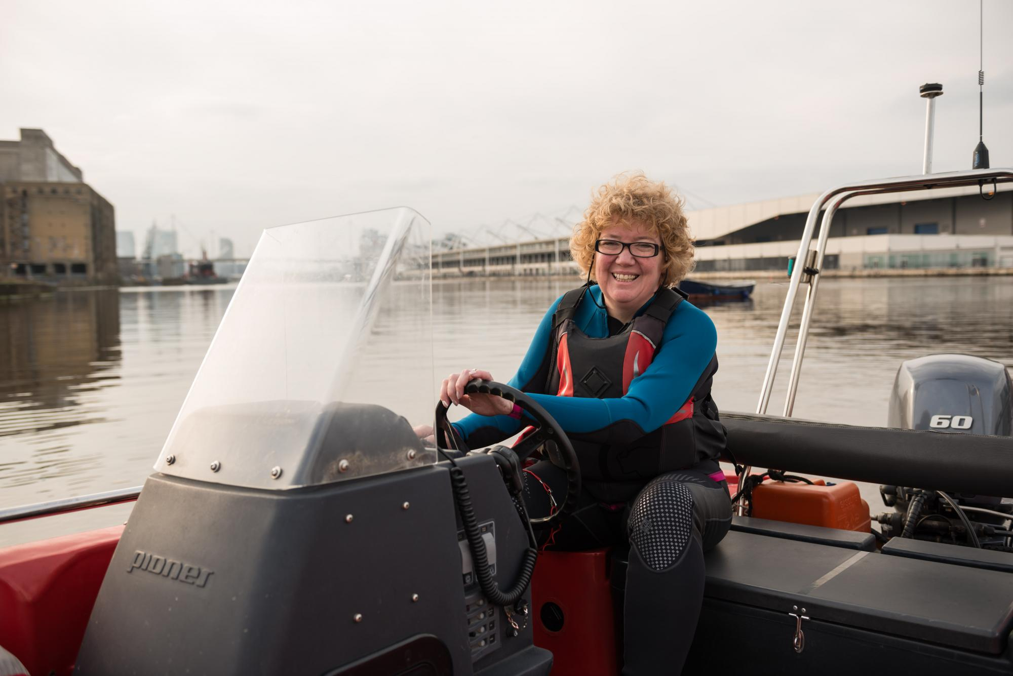Smiling lady volunteering as a watersports instructor and driving a boat