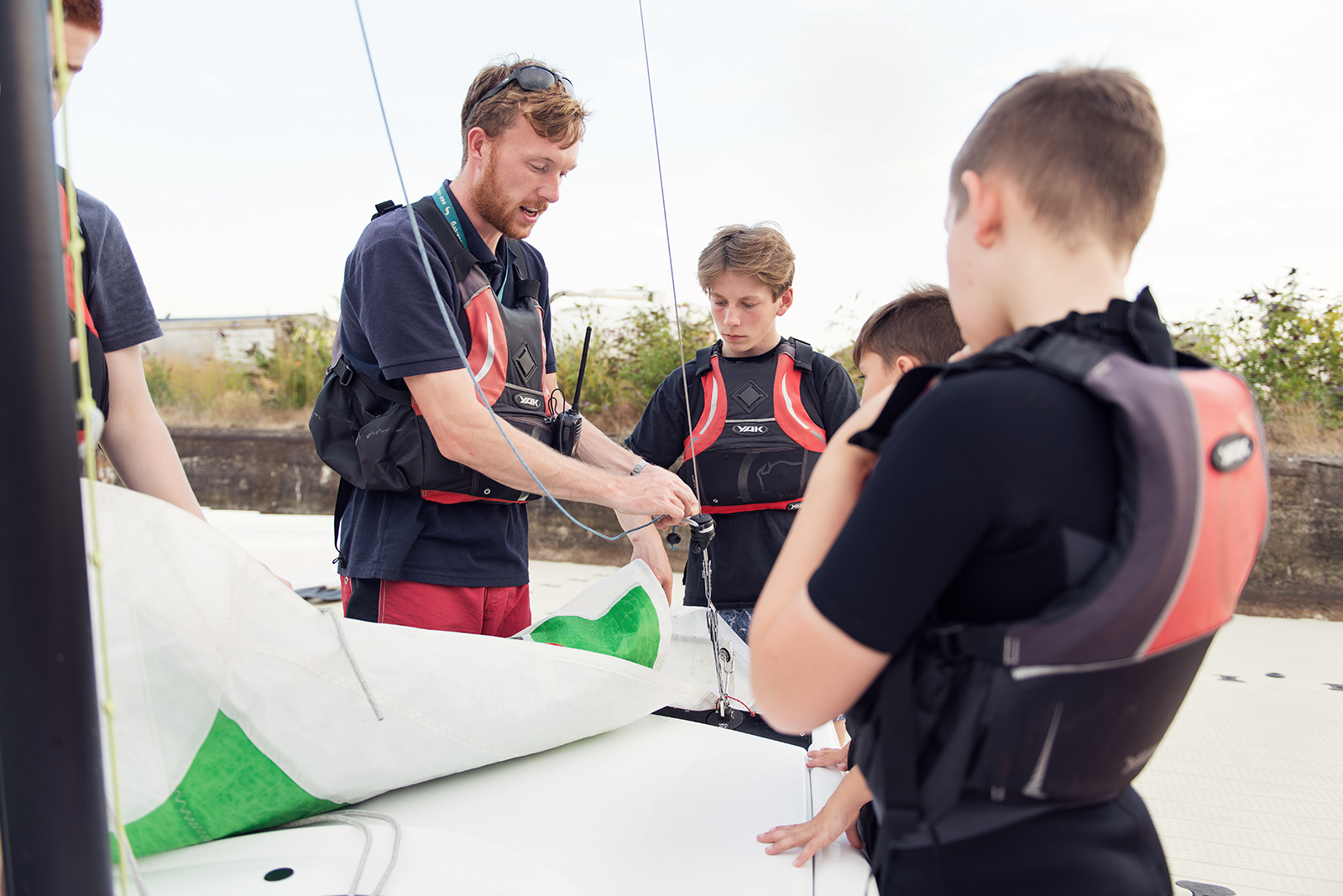 Instructor showing cadets how to attach a sail to a boat