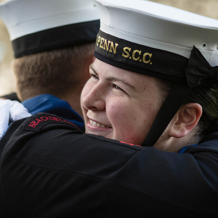 Two Sea Cadets smiling and hugging