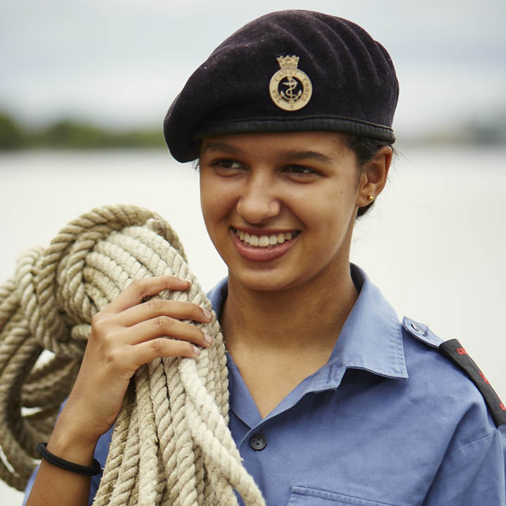 Girl Sea Cadet smiling and carrying rope