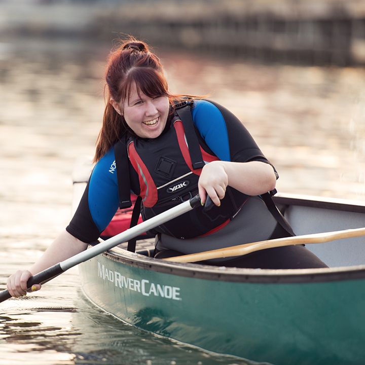 Smiling teenage girl rowing a boat