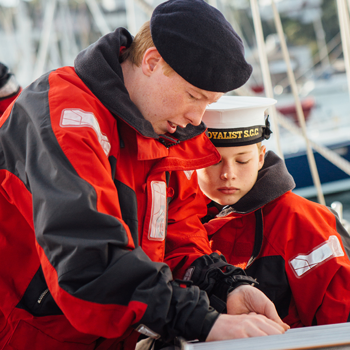 Adult volunteer showing a Sea Cadet a new skill