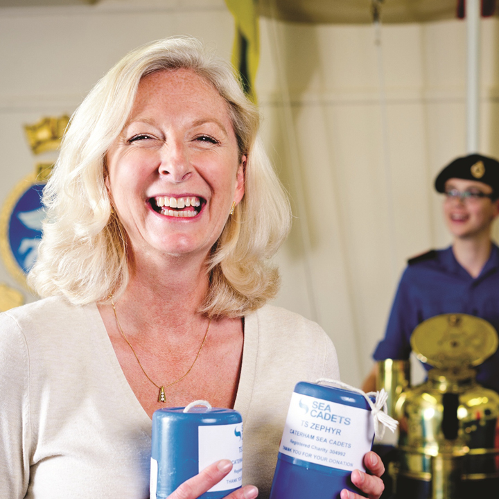 Smiling woman holding a Sea Cadet charity collection box