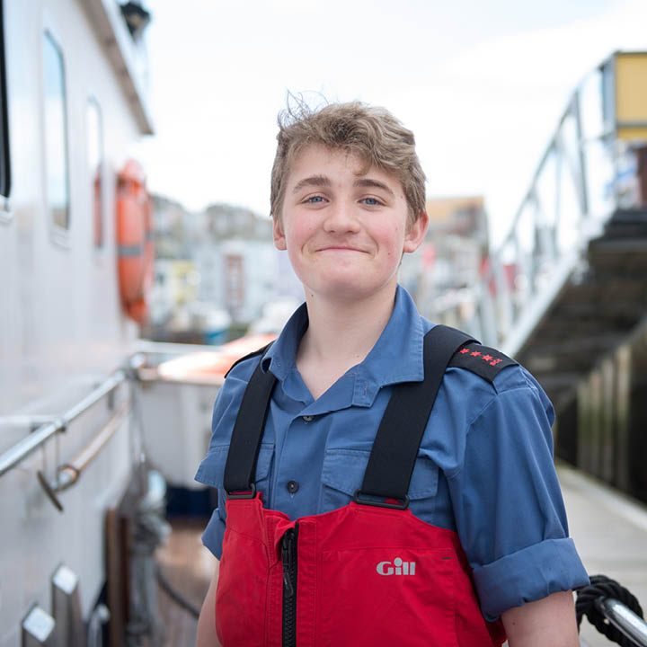 Boy Sea Cadet smiling in safety jacket by a ship
