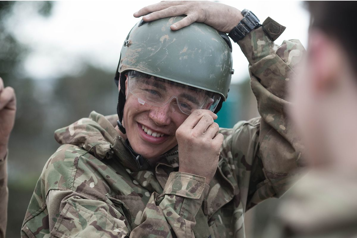 A smiling Royal Marines Cadet adjusting his helmet